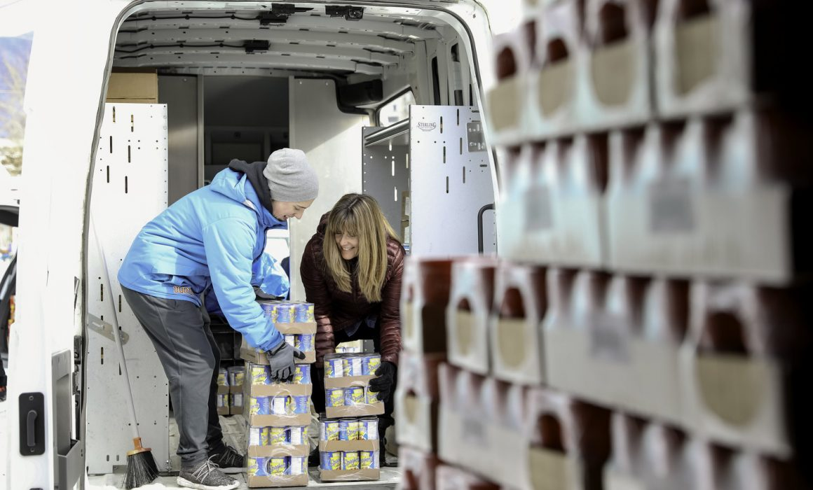 Two volunteers load packages of soup onto the Community First Foundation Van