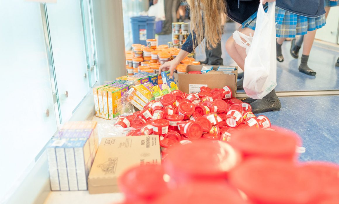 A volunteer packages food into a backpack