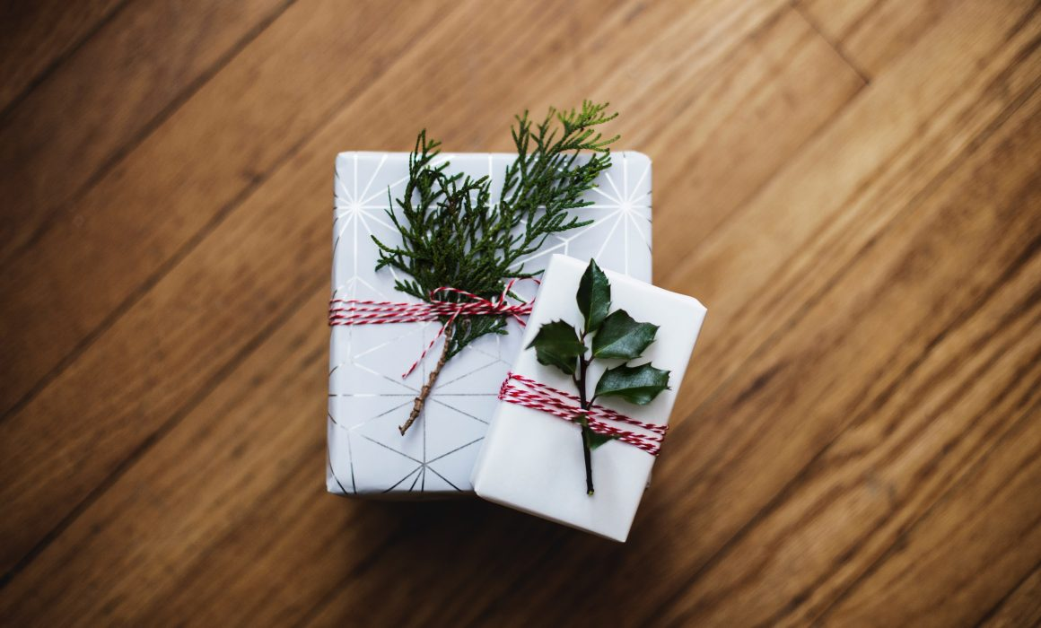 two gifts wrapped in white paper for employees holiday giving